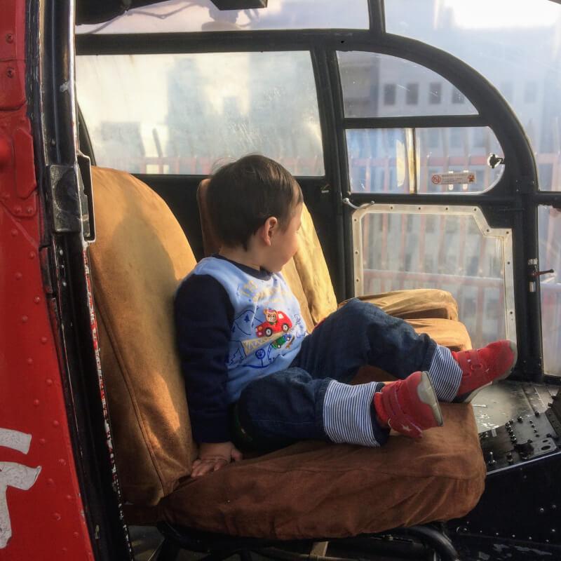 ヘリコプターの操縦席に座る息子