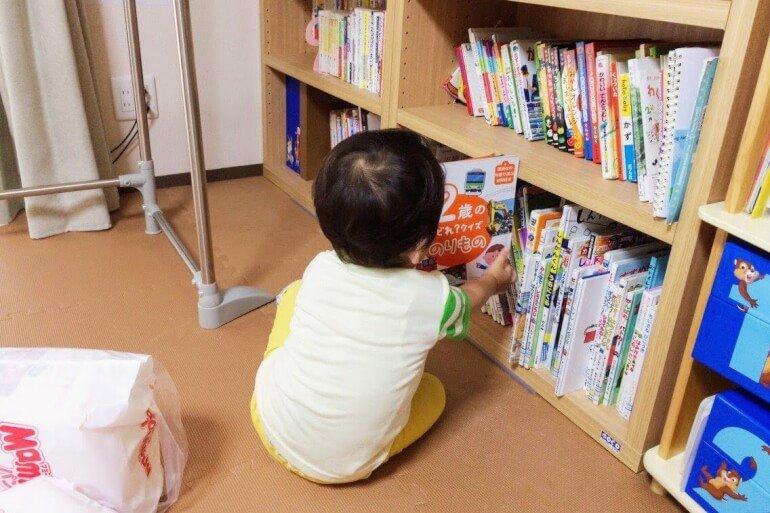 本棚から絵本を取り出す子供